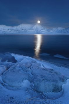 view over an arctic fjord lit by the light of the full moon during the polar night