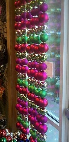 Christmas window treatment - get cheap ornaments at the dollar store, hang on fishing wire, knotting around the loop on each one, and then attach to a tension rod to display in window by margi.h