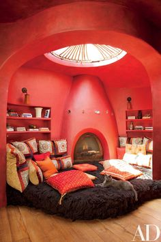 An ocular window casts light over Jada Pinkett Smith's vibrant, coral-color meditation space in the Malibu, California, home she shares with her husband, Will Smith. A large furry cushion, patterned throw pillows, and carefully arranged bookshelves encourage relaxation.