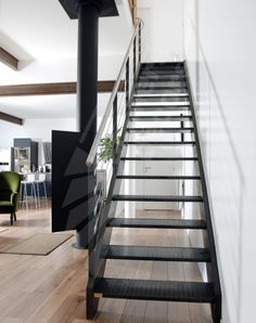 Photo DT38 - ESCA'DROIT®. Escalier métallique d'intérieur design pour une décoration de style industriel ou type loft. Marches caisson Nanoacoustic® tôle larmée anti-dérapante pour un escalier acier silencieux. Rampe avec option main courante en inox brossé et lisses en câble inox. Finition : acier brut patiné qui s'accorde parfaitement avec la finition de la cheminée design de chez Focus. - © Photo : Vanessa DESCHUYTENEER