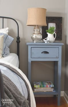 Black iron Ikea bed frame and DIY blue nightstand in rustic cottage bedroom - thegoldensycamore.com