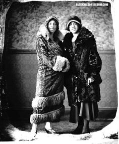 Two unidentified, fur-bedecked African American women dressed in classic flapper style smile for the camera, circa 1920s. African American vernacular photography via Black History Album via Flickr