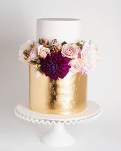 Beautiful white and gold cake topped with fresh pink and burgundy blooms  via…
