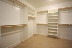 simple white closet with floating shelves and racks. contemporary closet by LuAnn Development, Inc.