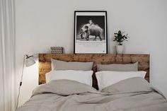 Drewniane wezgłowie łóżka w szarej sypialni