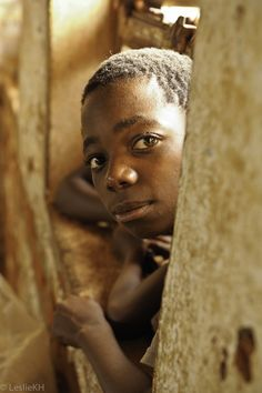 Photo 36 of 100: a curious student looks in on a Self Help Africa visit to Phirilanjuzi Primary School in Malawi.
