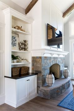 The fireplace features a stone base with white shiplap above and a white mantel with small corbels. It also features built-ins on both sides.