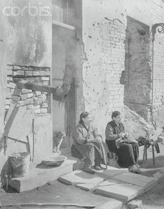 Original caption:Life Goes On. Warsaw, Poland: These aged Polish women are seated outside their wrecked home in an old section of Warsaw. They and their pet cat take advantage of the sunshine, one of the few essentials that were free and unrationed. Warsaw, once a thriving capital city, is now a ghost city from the many aerial attacks of World War II, and most of the inhabitants are undernourished and ill-clad. April 03, 1946