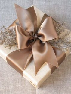 Neutral gift wrapping with ivory paper and large taupe ribbon and bow