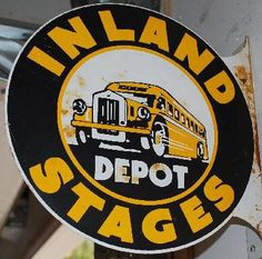 Flanged round sign for Inland Stage Bus Depot showing a bus in the center.