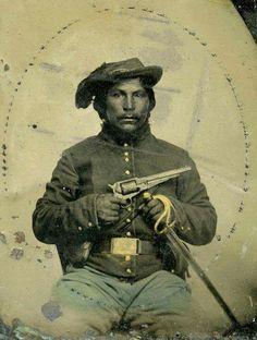 An unidentified union cavalry soldier, Indian home guard. The Indian home guard were Oklahoma native troops fighting for the union. He has an officers rank, by seeing part of an embroidered badge on his plume hat. He holds a .44 army revolver and a M1860 sabre.
