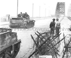 """Two soldiers of the US 82nd Airborne Division watch as Cromwell tanks of the Guards Armoured Division of the 2nd Armoured Recon Battalion the Welsh Guards cross Nijmegen bridge in Netherlands, Thursday, September 17, 1944. """"Market Garden"""""""