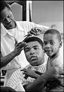 USA. Chicago, Illinois. 1966. Muhammad ALI in a barber shop getting a haircut