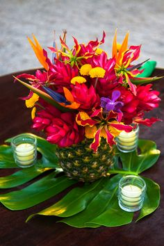 Ginger, mums, gloriosas, birds of paradise, orchids inside a natural pineapple on top of monstera leaf with candle votives