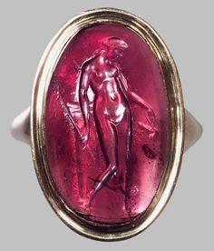 Gemme: Nackte Mänade mit Thyrsosstab und Phallos. Griechisch, Hellenistisch 2. Jh. v. Chr. Amethyst, kräftig violett, klar. In moderner Goldfassung als Ring.