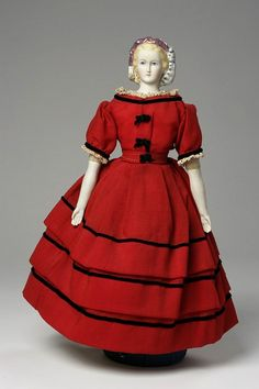 1868 Doll, moulded bisque shoulder head and lower limbs with a sawdust filled cloth body, painted facial features and moulded hair*; legs painted to show pink ribbons around the calves and black flat heeled lace up boots *blond hair covered with snood, trimmed with lustre clothing:  dress and cape, red wool with black velvet and ribbon trim petticoat, drawers and chemise, white cotton  flannel with bodice of heavy cotton