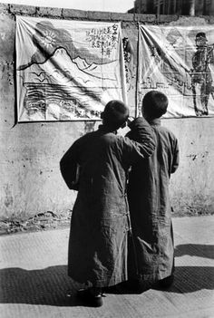 Two Chinese boys read banners celebrating the Chinese resistance to the Japanese occupation of China