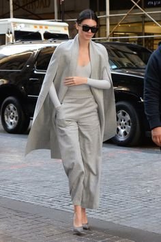 The model goes for head-to-toe grey in an Atea Oceanie grey bodysuit layered underneath a cape blazer and matching pants while in New York.