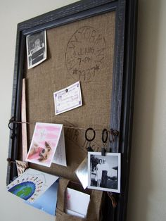 frame + fabric + wire/ribbon/string + curtain rings... a grouping of these would look awesome... you could make one for keepsakes from annual trips or one for each kid/family member