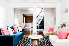 colorful living room white living room with navy sofa and spiral staircase