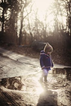 Little girl playing in a puddle on the road with trees in background