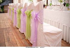 Chairs decorated with alternating color bows.