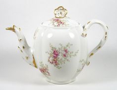 """Very good condition, very small chip on the spout and a small chip with a crack on the inside rim. Free of additional chips, cracks, repairs and crazing. Pretty hand colored transfer design of sprays of pink roses. The handle has a split design and both handle and spout are decorated with gold accents. The teapot has a pretty double flower finial. It holds 48 ounces and measures approx. 8"""" hing including the finial x 10"""" wide from handle to spout. Marked for Wm Guerin & Co. and ..."""