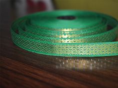 "Beautiful Green Color hand-loom border from India, Jacquard ribbon border trim. Trim is decorated with golden metallic thread embroidery.   ➤ This listing is sold by (8 yard) Width: 0.5 ""..."
