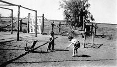 Two small children playing cricket in the farmyard at 'Wamberra' station. They are using a chair as wicket.  Place & Date Depicted:	Mildura District, Victoria, Australia, circa 1935