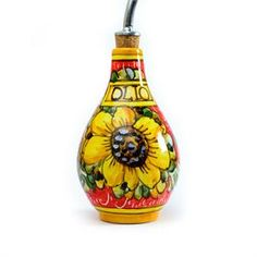 Oil Bottle - Sunflower on Red $39.95 Beautiful sunflower pattern oil bottle is skillfully crafted by a multi-generational family of artisans in a small town outside of Florence, Italy. •Dimensions: 6 inches height (8.5 inches with spout), 3.5 inches wide (4.5 inches with handle) •Pottery glazed with Maiolica  •Handmade and painted in Italy •Lead free •Food safe, hand washing recommended •Stainless steel spout with cork stopper included