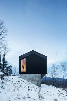 A country house is located on the top of a sloped land surrounded by a forest in Bolton East, Quebec, Canada. The architecture studio Nature Humaine designed the project having in mind the client's special request of a house in perfec Architecture Design, Residential Architecture, Dezeen Architecture, Winter Cabin, Cozy Winter, Mountain Homes, Black House, Minimalist Home, Minimalist Interior