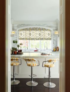 arched roman shade in ikat, sunny pattern on barstools