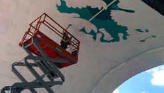 Edmonton artist Jill Stanton painting second Hunter St. bridge mural in Peterborough. By Bruce Head. Stanton's bloodroot-themed design expected to be completed by September.