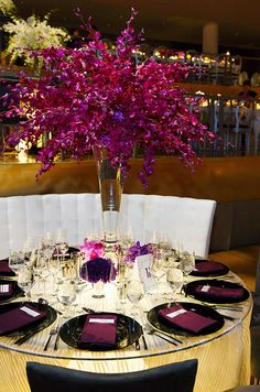 A towering centerpiece of purple orchids decorates an elegant round wedding reception table.