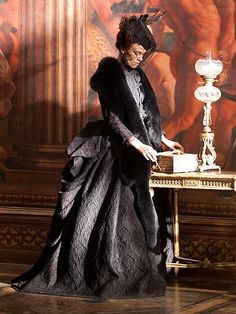 Anna Karenina - Keira Knightley as the protagonist wearing a black brocade dress with matching fur stole and pillbox hat with veil.