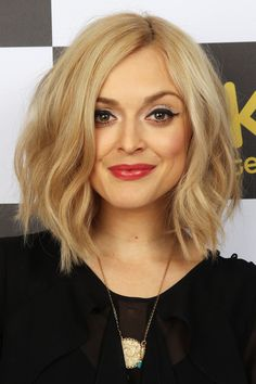 Shoulder length wavy blonde bob haircut with a side part hairstyle