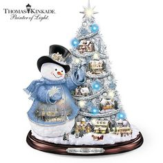 Deck the Halls. Thomas Kinkade Pre-Lit Tree And Snowman Tabletop Decor. A fully-sculpted Kinkade snowman, a lighted village and a pre-lit holiday tree all rest on a mahogany-toned base. Pre Lit Christmas Tree, Tabletop Christmas Tree, Holiday Tree, Blue Christmas, Christmas Snowman, Christmas Tree Decorations, Christmas Mantles, Snowman Decorations, Magical Christmas
