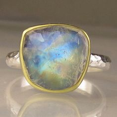 Flashy free form rose cut rainbow moonstone set in 18k bezel on hammered sterling silver band(2.5mm wide). The moonstone has a backsheet of fine