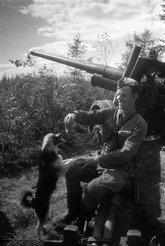 Soviet soldier feeding his doggy on the frontline in between battles.