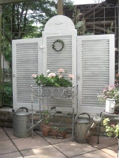 Repurposed shutters are used as a garden screen.