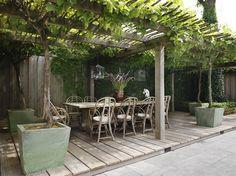 Een sfeervol houten terras wordt overkapt door een pergola met een lattendak. Het groen op het dak maakt de sfeer compleet.