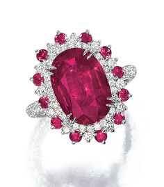 RUBY AND DIAMOND RING, MICHAEL YOUSSOUFIAN. The oval ruby weighing 5.33 carats, set within a circular-cut ruby and brilliant-cut diamond cluster surround, the shoulders and shank set with similarly cut diamonds, mounted in white gold,