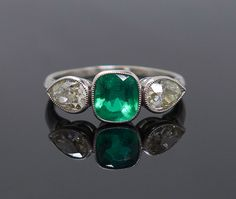 This striking ring dates to the Art Deco era of the 1930s. The hand fabricated platinum ring features a square Colombian emerald flanked by two bezel set pear shaped diamonds. The bezel set emerald is a square cushion modified brilliant cut natural type III. It measures 6.52 x 6.01 x 4.23mm with an approximate weight of 1.10ct. The diamonds are VS-2 to SI-1 in clarity and N-O in color. Each diamond measures about 6.16 x 4.47 x 2.87mm for an approximate total weight of 0.95ct. The size 8 ring…