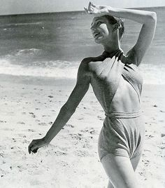 Model in McCardell's milestone bathing suit of pale grey jersey, the halter top is wrapped around the neck and anchored to diaper trunks below a completely bare back, photo by Louise Dahl-Wolfe, 1945