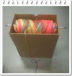 Simple but ingenious way to hold your yarn while crocheting.  Box, one large knitting needle, and yarn.
