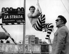 Photograph:Celebrated Italian director Federico Fellini, right, and actor Richard Basehart prepare to shoot a scene from La Strada (1954). The clapboard shows the scene and take numbers.