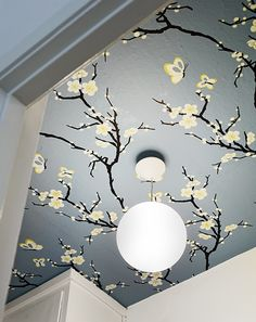 Creative way to use a wallpaper: on the ceiling! Looks enchanting!.........the simple circular light fixture is what is majorly creating the enchanting effect........very adorable!!.......Plain simple walls are apt if a designer ceiling is to be created.