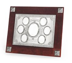 A Russian silver photograph frame, the large central oval aperture surrounded by six smaller apertures, all with hinged covers mounted with beveled glass, all interlaced with an engraved ribbon border and scrollwork, set with a border pierced with geometric ornament, mounted over red velvet, the corners set with square bosses, the back with velvet-covered strut, with partially obscured maker's mark in addition to that of Ovchinnikov, Moscow, 1877. Sotheby's