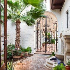 Spanish Hacienda Design, iron gate, brick walk, outside sitting area