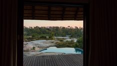 A slow linear dolly shot from the inside of a luxurious private African lodge with a view onto the patio deck with swimming pool and river in the distance at dawn, just before sunrise. Before Sunrise, Kruger National Park, Stock Footage, Distance, Dawn, Swimming Pools, Shots, Trees, African